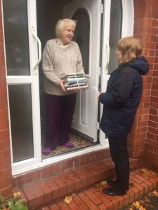 Lady receiving a bundle of books as part of the delivery service